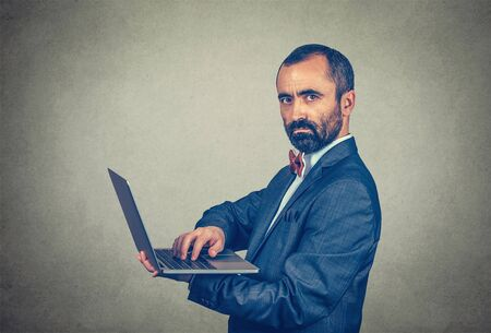 Closeup portrait of man with laptop computer on the arm looking at you camera serious. Mixed race bearded model isolated on gray studio wall background with copy space. Horizontal image.