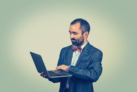 Young handsome mature middle age business man connecting to internet using looking attentively in a laptop. Mixed race bearded guy isolated on green studio wall background with copy space. Horizontal