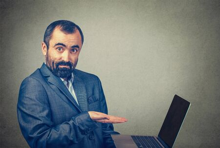 Closeup portrait of mature middle age business man showing pointing presenting a laptop screen with an open palm. Mixed race bearded model isolated on gray studio wall background with copy space. Banco de Imagens