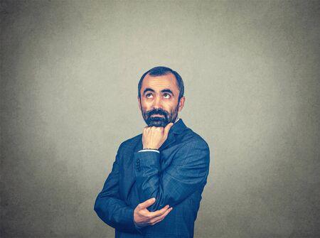 Porträtnahaufnahme eines gutaussehenden nachdenklichen Mannes mit Bart, der die denkende Faust am Kinn nachschaut Gemischtes bärtiges Modell einzeln auf grauem Studiowandhintergrund mit Kopienraum. Horizontal