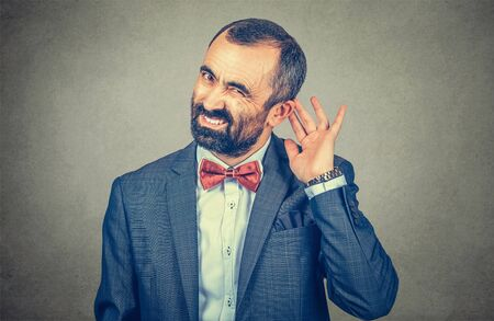 A mature, middle-aged man holds his hand near ear and listening trying to hear. hearing, deaf problem concept. Mixed race bearded model isolated on gray studio wall background with copy space Banco de Imagens