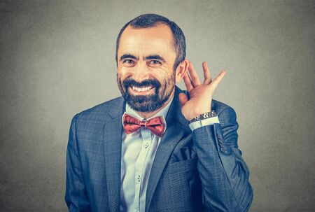 man eavesdropping laughing happy, businessman with his hand to his ear trying to listen smiling looking at you camera. Mixed race bearded model isolated on gray studio wall background with copy space