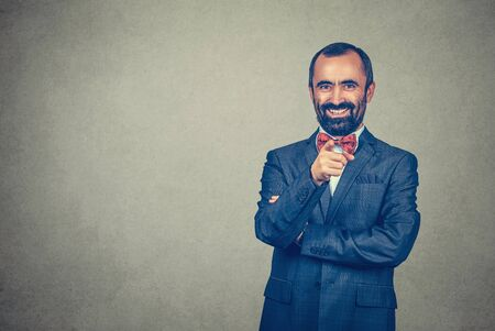 Handsome mature middle aged man pointing finger at you smiling happy. Mixed race bearded model isolated on gray studio wall background with copy space. Horizontal image.