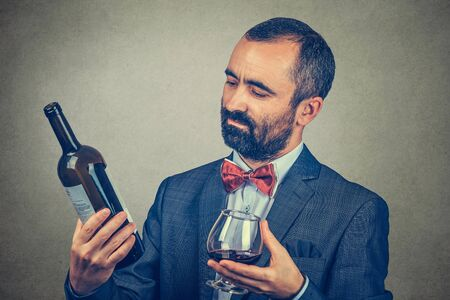 A man with a glass of wine holding, looking at a a bottle, reading the information on it. Mixed race bearded model isolated on gray background. Horizontal image. Vintner analyzing wine concept