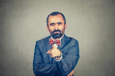 Ritratto di un uomo d'affari di mezza età maturo arrabbiato e infastidito che punta il dito contro di te gesto della fotocamera. Modello barbuto di razza mista isolato sul fondo grigio della parete dello studio con lo spazio della copia. Immagine orizzontale.