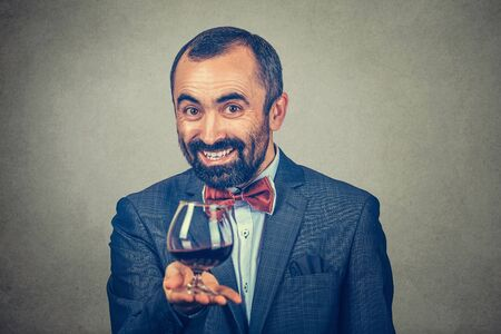 A mature happy man holding showing offering a glass of red wine looking at you camera smiling happily. Mixed race bearded model isolated gray background. Horizontal image. Winemaker waiter concept
