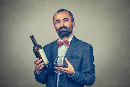 A man holding showing offering a glass of wine and a bottle looking at you camera smiling. Mixed race bearded model isolated gray background with copy space. Horizontal image. Winemaker waiter concept