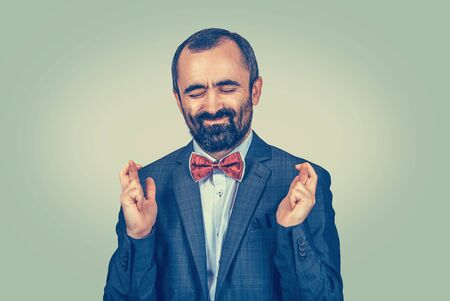 Closeup portrait of mature middle aged funny guy, business man crossing fingers, wishing, hoping for best, miracle isolated on green background. Human emotions, facial expression feeling attitude Banco de Imagens