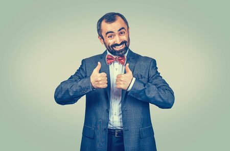 Happy mature middle-aged bearded smiling man giving thumbs up like, good review sign with both hands. Mixed race bearded model isolated on green yellow studio copyspace background. Horizontal image