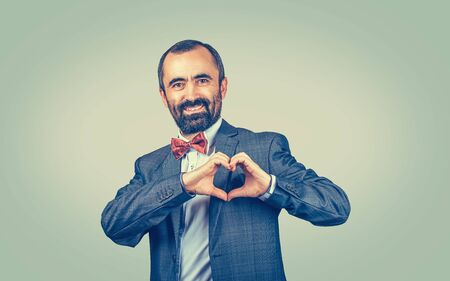 Handsome smiling mature middle-aged man makes heart shape with fingers, hands, isolated on green yellow wall background. Positive human emotion facial expression feeling body language attitude