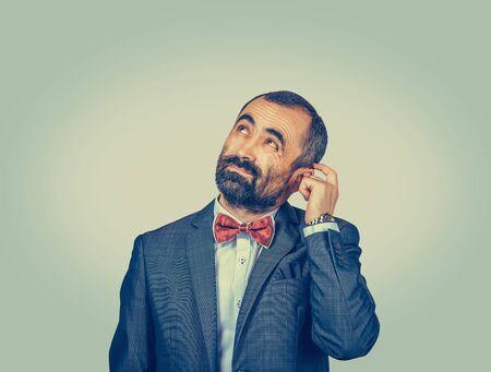 Closeup retrato hombre rascándose la cabeza, pensando profundamente en algo, mirando hacia arriba, aislado sobre fondo de pared verde-amarillo. Expresión facial humana, emoción, sentimiento, lenguaje corporal de signos Foto de archivo