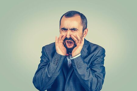 Closeup portrait headshot displeased angry man screaming holding hands near mouth to yell louder. Mixed race bearded model isolated on green studio wall background with copy space. Horizontal image.