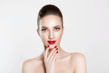 Beauty. Beautiful brunette woman with lovely natural skin and green grey eyes posing with naked shoulders isolated white background wall. Red and black gradient nails manicure and lips combination set