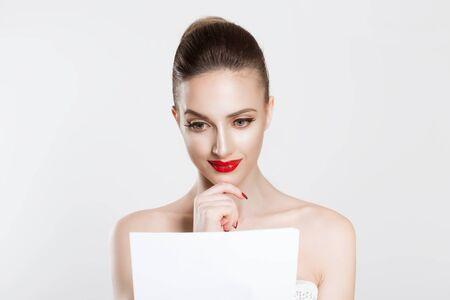 Actress learning role lines, bride reading her vow, bridal speech Beautiful happy brunette girl on white light grey background looking at document papers studying marital wedding contract. full makeup