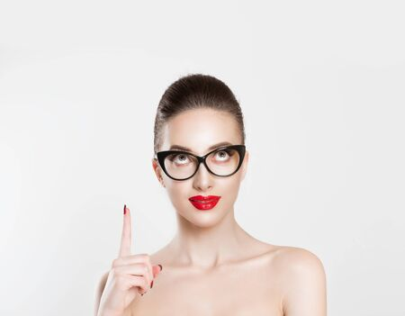 Look up here. Closeup brunette smart young woman pretty smiling girl in eye glasses nude makeup red lips idea looking up pointing with finger at blank copy space retro vintage hairstyle. Body language