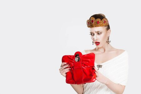 The princess looked into the red bag and was surprised to forget lost something has no more money. White light grey background wall. I am broke concept