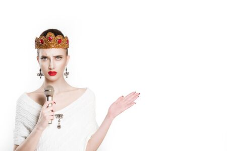 Frustrated beauty queen speaking on microphone gesturing anger with hand isolated white background wall. Angry Girl with golden ruby crown jewelry  red lips perfect makeup and mic. Modern journalist Stock Photo