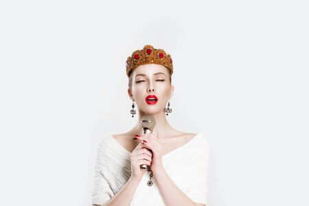 Retro singer. Beauty queen speaking singing karaoke on microphone isolated white background wall. Angry Girl with golden ruby crown jewelry red lips perfect makeup, mic. Modern journalist propaganda