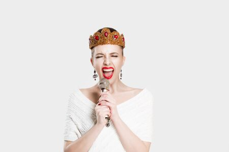 Frustrated singer. Beauty queen singing screaming on microphonehand isolated white background wall. Angry Girl with golden ruby crown jewelry  red lips perfect makeup and mic. Modern journalist