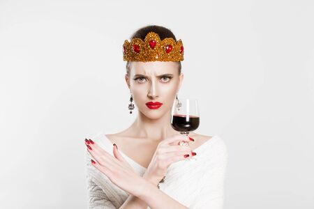Stop drinking alcohol, be responsible. Woman crowned beauty queen unhappy frustrated showing stop no with hands gesture holding glass of wine negative face expression isolated white background wall Stock Photo