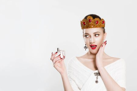 Wow, amazing my favorite perfume it's on sale. Surprised woman beauty queen crowned girl looking at a new perfume fragrance excited isolated white background wall Banque d'images