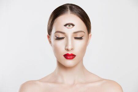 Psíquico. Mujer con 3 tercer ojo mirando su cámara concentrando el pensamiento con la mente y la intuición del corazón sobre el problema aislado fondo gris blanco. Hacer una decisión inteligente para encontrar el concepto de solución Foto de archivo