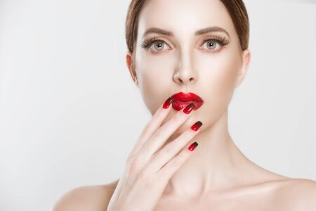 Beautiful sexy vamp woman with dark red  gradient black lips and modern same color set nail polish. Closeup Beauty fashion model girl portrait over white grey background. Nude Makeup false Long Lashes