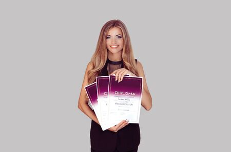 Half body view of woman holding a three diplomas for eyelashes extension courses isolated on gray grey background