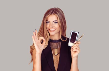 Content woman holding eyelash extension instruments and tools holding okay sign hand gesture approving beauty procedure and smiling at camera.
