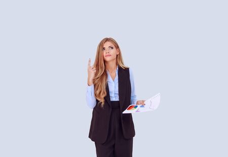 Angry woman looking up skeptically holding business papers. Showing look up here attention listen to me sign gesture with one hand and holding papers with graphics in other hand isolated on light blue