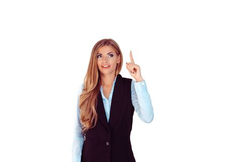 Look up here. Portrait happy beautiful woman having idea pointing up with finger at blank copy space isolated light gray white background. Positive human face expression emotion body language perception