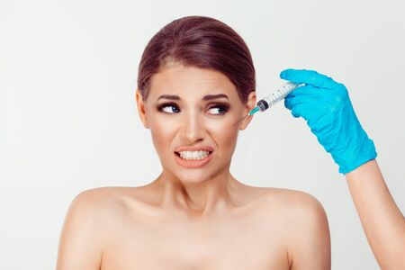 Woman looks to the syringe, is afraid of aesthetic surgery hyaluronic acid shot in her cheek, isolated on white background