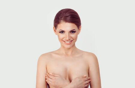 Breast Cancer Awareness. Middle age female exams breast for signs cancer by hands. Happy smiling daydreaming awaiting for mammal breast augmentation cosmetic plastic surgery looking at camera on white