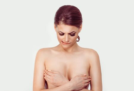 Brest cancer suspicion. Woman covers her breasts with her hands looking doubtful skeptical at tits while passes medical check for breast cancer. Isolated white background 스톡 콘텐츠