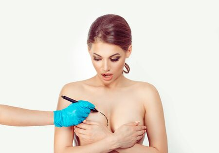 Cancer awareness. Shocked woman wonders about correction to make by her doctor to her breasts on white background. hand glove drawing cut line for plastic surgery breast augmentation removal reduction 스톡 콘텐츠