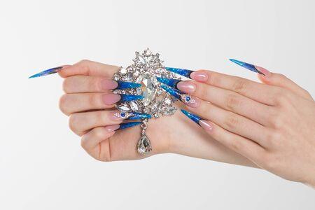 Nail Polish. Art Manicure. Modern style blue Nail Polish. Beauty hands holding white crystals gem stones diamonds broach showing its beauty. Stylish Colorful stiletto Nails isolated white background