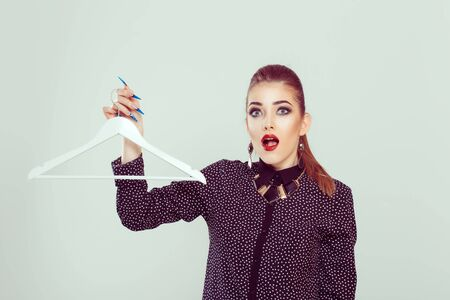 Sale, shopping concept. I have nothing to wear. An astonished surprised business woman holds a hanger for his clothes, looking at you camera isolated white background. Full makeup girl in black blouse