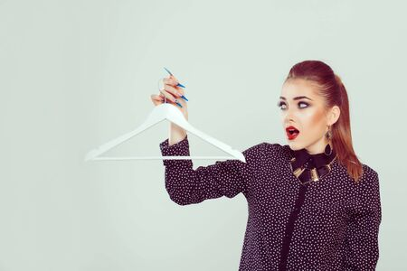 Sale, Need of shopping concept. I have nothing to wear. An astonished surprised woman holds a hanger for his clothes, looks at it isolated on a white background wall. Full makeup girl in black blouse Stok Fotoğraf