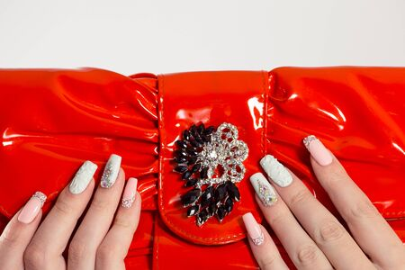 Nail Polish. Art Manicure. Modern style blue Nail Polish. Beauty hands holding red bag clutch purse. Stylish pastel Color pink white Nails isolated white background. Classic wedding bride nails design