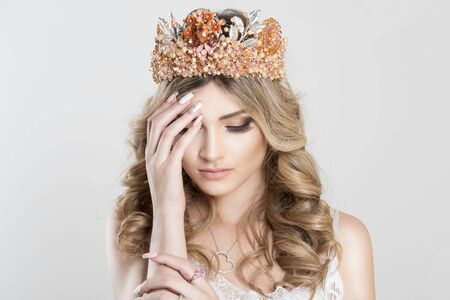 Sad Beautiful blonde girl in a golden crown on white grey background, eyes closed looking down with grief hand on shoulder pink ring on it