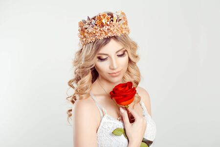 Beautiful like a flower. Closeup portrait blonde beauty curly girl with silver pink crown holding looking at red rose isolated white grey background wall