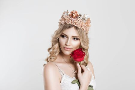 Beauty Queen bride with bright pink crown holding a red rose near her cheek looking side wards, light bridal makeup isolated grey white background wall 免版税图像 - 139602744