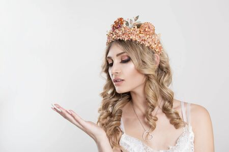 Beauty crowned queen girl woman actress miss bride looking down showing to side sidewards copy space with hand isolated white background wall. Full makeup diamond golden pink crown nails pastel color