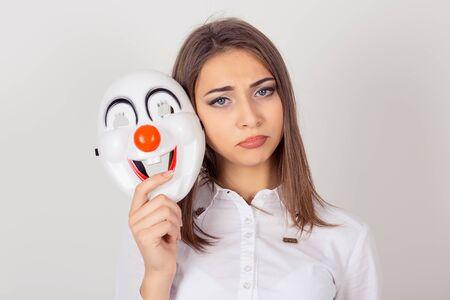 Llevando una máscara, fingiendo su concepto. El retrato del primer preocupaba a la muchacha con la expresión triste que sostenía una máscara del payaso que expresaba la felicidad, mirando la cámara, fondo blanco aislado. Bipolar. Sensación de expresión facial