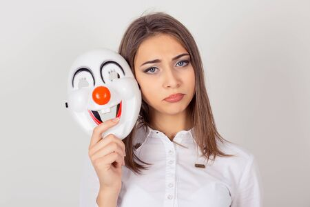 Wearing a mask, faking it concept. Closeup portrait worried girl with sad expression holding a clown mask expressing happiness, looking camera, isolated white background. Bipolar. Facial expression feeling