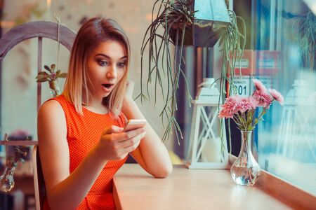 Single amazed girl watching content on a smart phone at home in a coffee shop