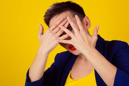 Closeup scared woman covering face with hands hiding face looking peering peeking through fingers on yellow background. Family problems and woman violence cover face fight fear, afraid, abused girl