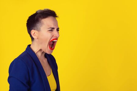 Profile portrait angry upset woman screaming crying wide open mouth hysterical face grimace isolated yellow wall background. Negative human expression emotion reaction. Conflict confrontation concept