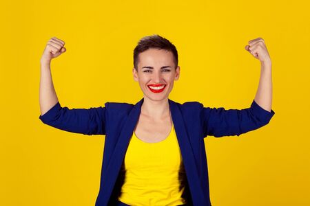 I am powerful and happy. Portrait of a happy elegant business woman showing power her biceps on yellow background. Multicultural Latina girl short hair red lips blue suit yellow shirt