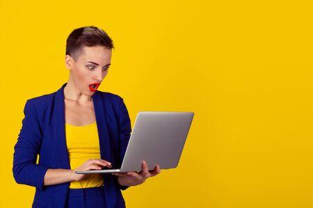 Surprised Shocked young business woman short hair using laptop looking at computer screen blown away in stupor on yellow background. Human face expression, emotion, feeling, body language, reaction Stock Photo